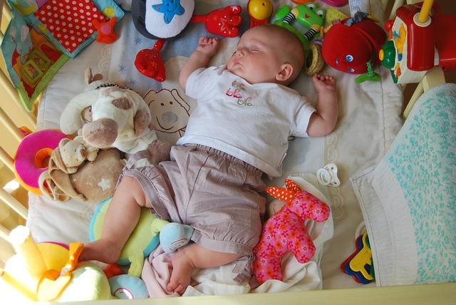 miminko spící v postýlce s hračkami