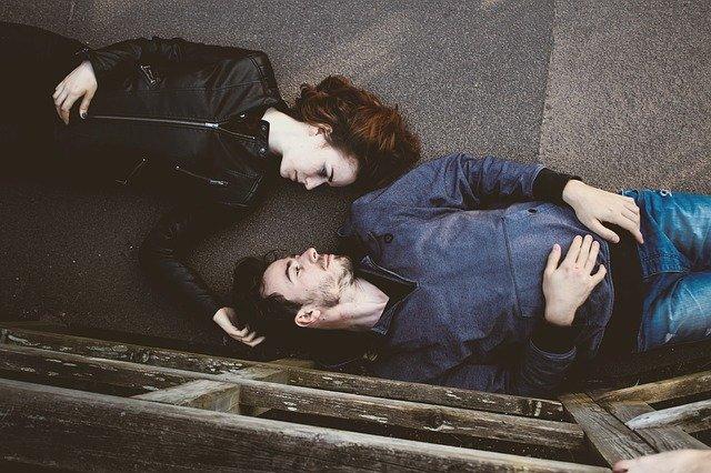 muž a žena leží na asfaltu